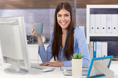 secretary desk: Portrait of happy businesswoman sitting at office desk with coffee mug handheld, smiling at camera.