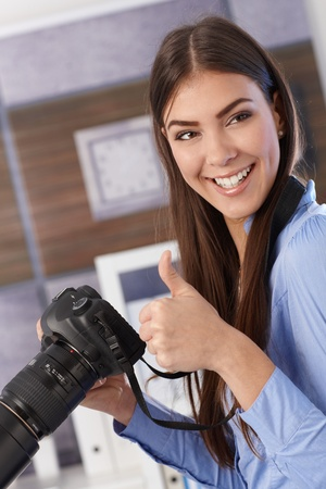 Pretty photographer girl holding camera, laughing, giving thumb up. photo