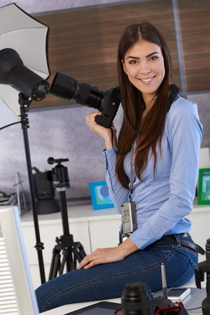 Portrait of beautiful photographer in studio, holding camera, smiling, photo