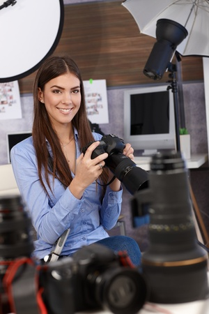portrait young girl studio: Beautiful photographer girl sitting in studio with camera handheld, surrounded by camera lens and equipment, selective focus. Stock Photo