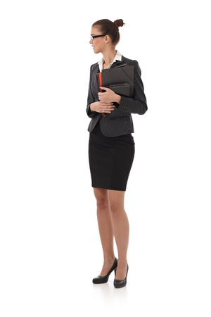 Pretty businesswoman standing with folders handheld, full size side view portrait. photo