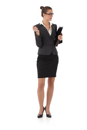 Attractive businesswoman with documents handheld, gesturing, smiling, cutout on white. photo