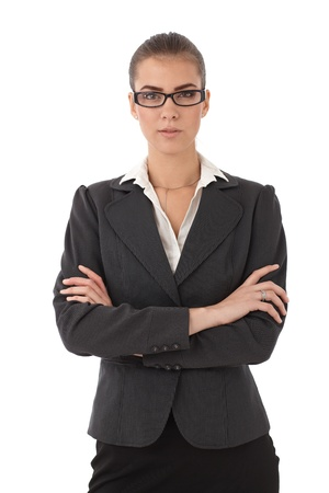 strict: Portrait of young strict businesswoman with arms folded, looking at camera. Stock Photo
