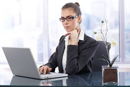 Smart businesswoman with glasses working on laptop computer at office table. photo