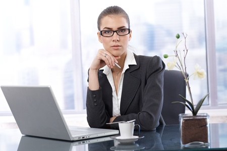 Businesswoman at work, sitting in office with laptop computer, having coffee, holding pen, looking at camera. photo