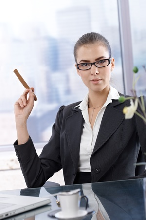 Confident smart businesswoman posing at skyscraper office with cigar handheld. photo