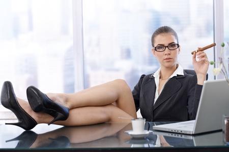 cigarro: Hot empresaria sentado con los pies zapatos de tac�n alto en el escritorio de la oficina, la celebraci�n de cigarro, mirando a la c�mara con seguridad.