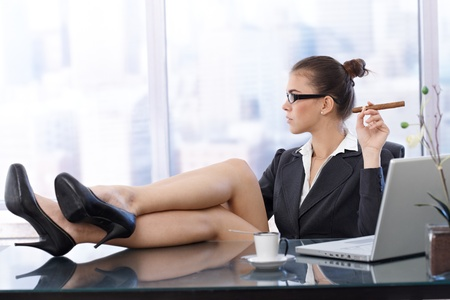 view of an elegant office: Cool businesswoman with feet up on desk, wearing high heels, having coffee, cigar handheld, side view in skyscraper office. Stock Photo