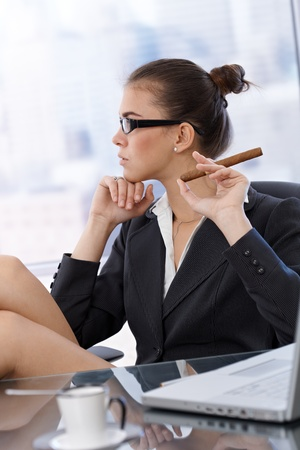 view of an elegant office: Profile portrait of trendy businesswoman with cigar handheld, sitting at office table.