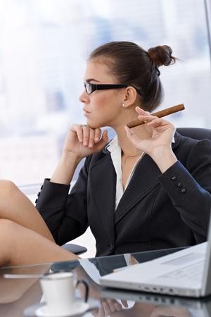 perfil de mujer rostro: Retrato de perfil de la empresaria de moda con mano cigarro, sentado a la mesa de oficina.