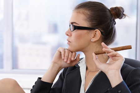 Portrait of cool businesswoman in trendy glasses with cigar handheld, thinking, side view. photo