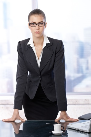Smart attractive businesswoman standing in skyscraper office leaning on table, looking at camera confidently. photo