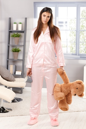 displeased: Portrait of attractive sleepy woman standing in pyjama with teddy bear and coffee mug handheld in living room.