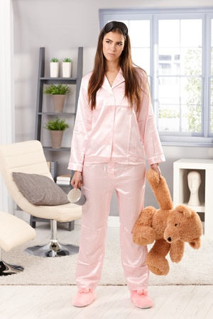 Grumpy sleepy woman in trendy pyjama standing with coffee mug and teddy bear handheld in living room, looking annoyed. photo