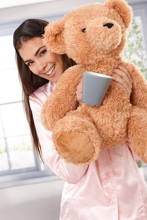 Portrait matin heureux de sourire jolie femme portant pyjama avec ours en peluche et une tasse de café.