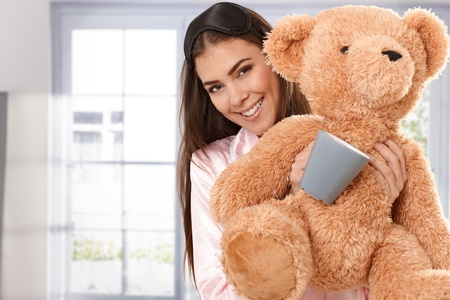 wake up happy: Happy woman cuddling with teddy bear and coffee mug in morning, smiling at camera. Stock Photo