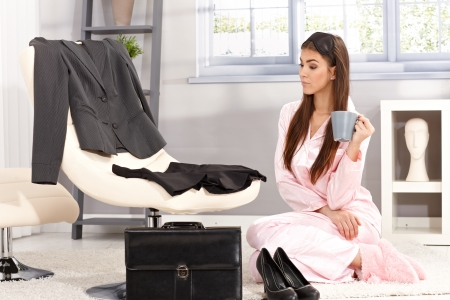 getting ready: Sleepy businesswoman getting ready for work in morning, sitting in pyjama in living room having coffee. Stock Photo