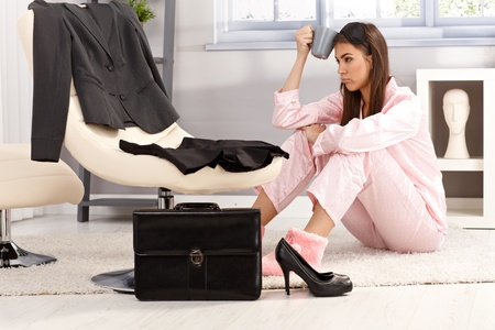 formal dressing: Tired woman getting ready for business work, sitting in pyjama on living room floor, holding coffee mug, annoyed. Stock Photo