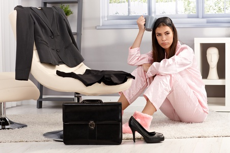 formal dressing: Displeased tired young woman in pyjama getting ready for work, sitting on living room floor surrounded with business clothes and briefcase, having coffee.
