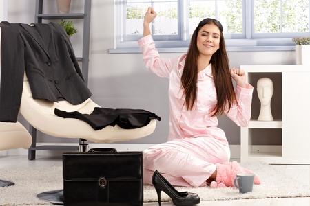 formal dressing: Happy woman stretching in pyjama in morning, sitting on living room floor, getting ready for business work.
