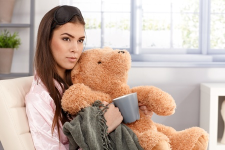 Morning portrait of sleepy young woman cuddling with teddy bear and blanket, holding coffee mug, wearing eye cover and pyjama, sitting in living room. photo