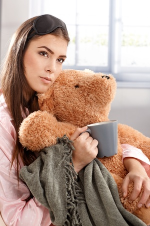 levantandose: Retrato de joven mujer en pijama y antifaz para dormir, tomando café, abrazo por la mañana con osito de peluche y una manta.