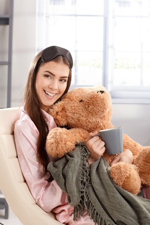 Morning portrait of laughing woman cuddling with teddy bear and blanket at home, wearing pyjama and eye cover. photo