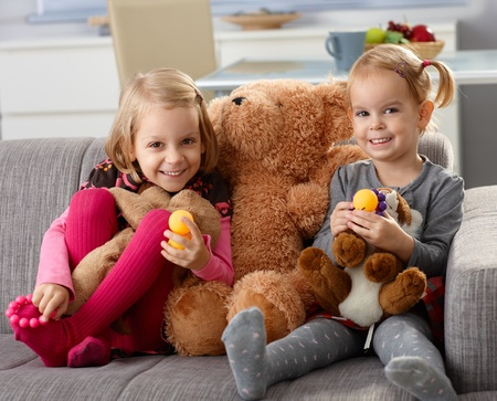 Little sisters smiling happily at home, sitting on sofa with big teddy bear. photo