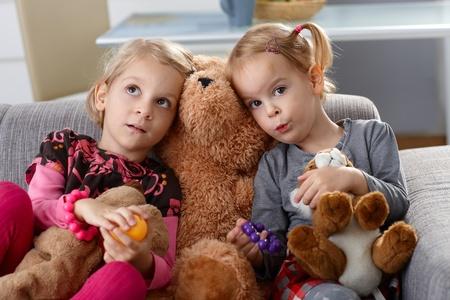 2 to 3 years: Le bambine seduto sul divano con orsacchiotto tra di loro.