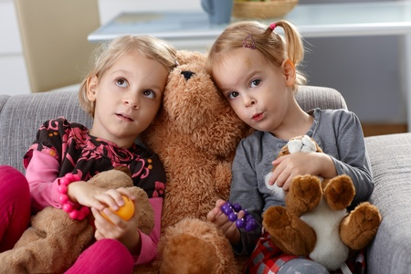 3 5 years: Little girls sitting on sofa with teddy bear between them.