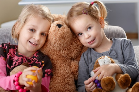 huddling: Little girls on sofa huddling up against teddy bear, smiling. Stock Photo