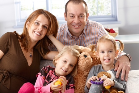 Happy family with two daughters and pregnant mother at home. photo