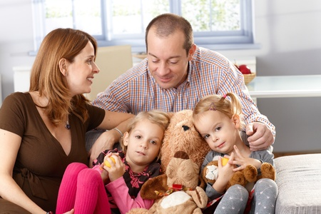 Happy family with two daughters and pregnant mother sitting on sofa. Stock Photo - 13139199