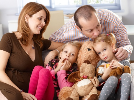 be kissed: Family with two daughters and pregnant mother sitting on sofa at home, father kissing daughter. Stock Photo