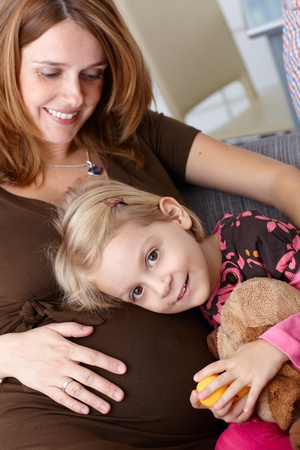 Little girl huddling up against pregnant mothers belly, smiling happily. photo