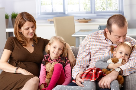 be kissed: Happy family with two daughters and pregnant mother sitting on sofa at home, smiling.