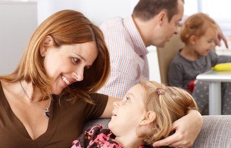 family of five: Mother and little daughter looking to each others eyes smiling happily.