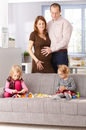 Little girls playing at home on sofa, parents standing behind, woman expecting a baby. Stock Photo - 13139232