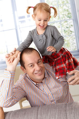 Happy father and little daughter playing at home, little girl climbing on father's shoulder, laughing. Stock Photo - 13139223
