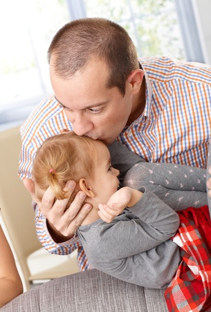 be kissed: Father kissing little daughters head, little girl smiling happily. Stock Photo