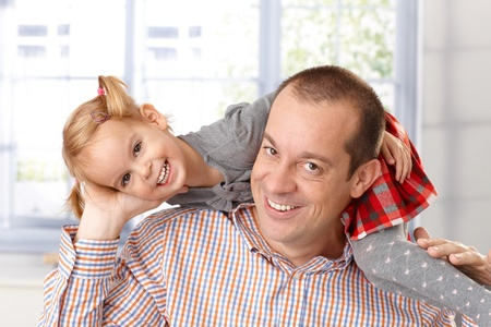indoor photo: Little daughter around fathers neck having fun, both laughing.