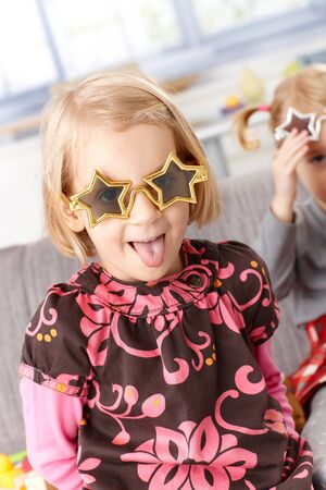 Little girl playing at home, sticking tongue wearing funny star shaped glasses. photo