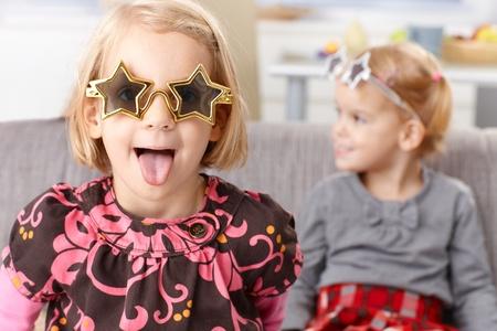 falta de respeto: Ni�a rubia que se divierte en casa, que pega la lengua, con gafas graciosas en forma de estrella, la hermana peque�a en el fondo. Foto de archivo