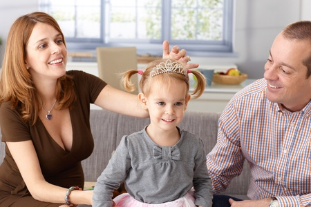 Little princess in tiara smiling, pregnant mother and father adoring. Stock Photo - 13138992