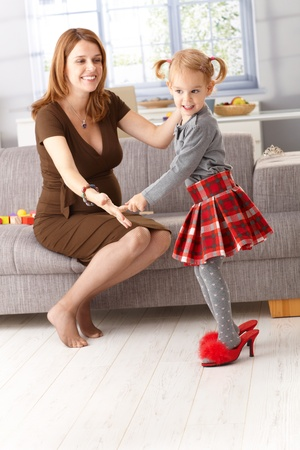 3 4 length: Little girl posing in mothers high heel red slippers, having fun. Stock Photo