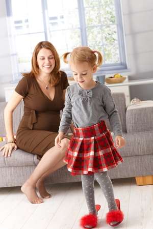 Little girl wearing mother's high heel red slippers, pregnant mother watching from background. Stock Photo - 13138740