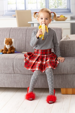 little girl sitting: Cute little girl eating banana, wearing mothers high heel red slippers. Stock Photo