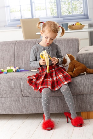 3 year old little girl eating banana at home, sitting on sofa, wearing high heel red slippers. Stock Photo - 13139234