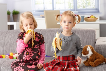 Little sisters eating banana at home, sitting on sofa. photo