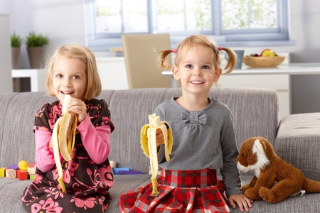 Happy little girls eating banana at home, sitting on sofa, smiling. Stock Photo - 13139221